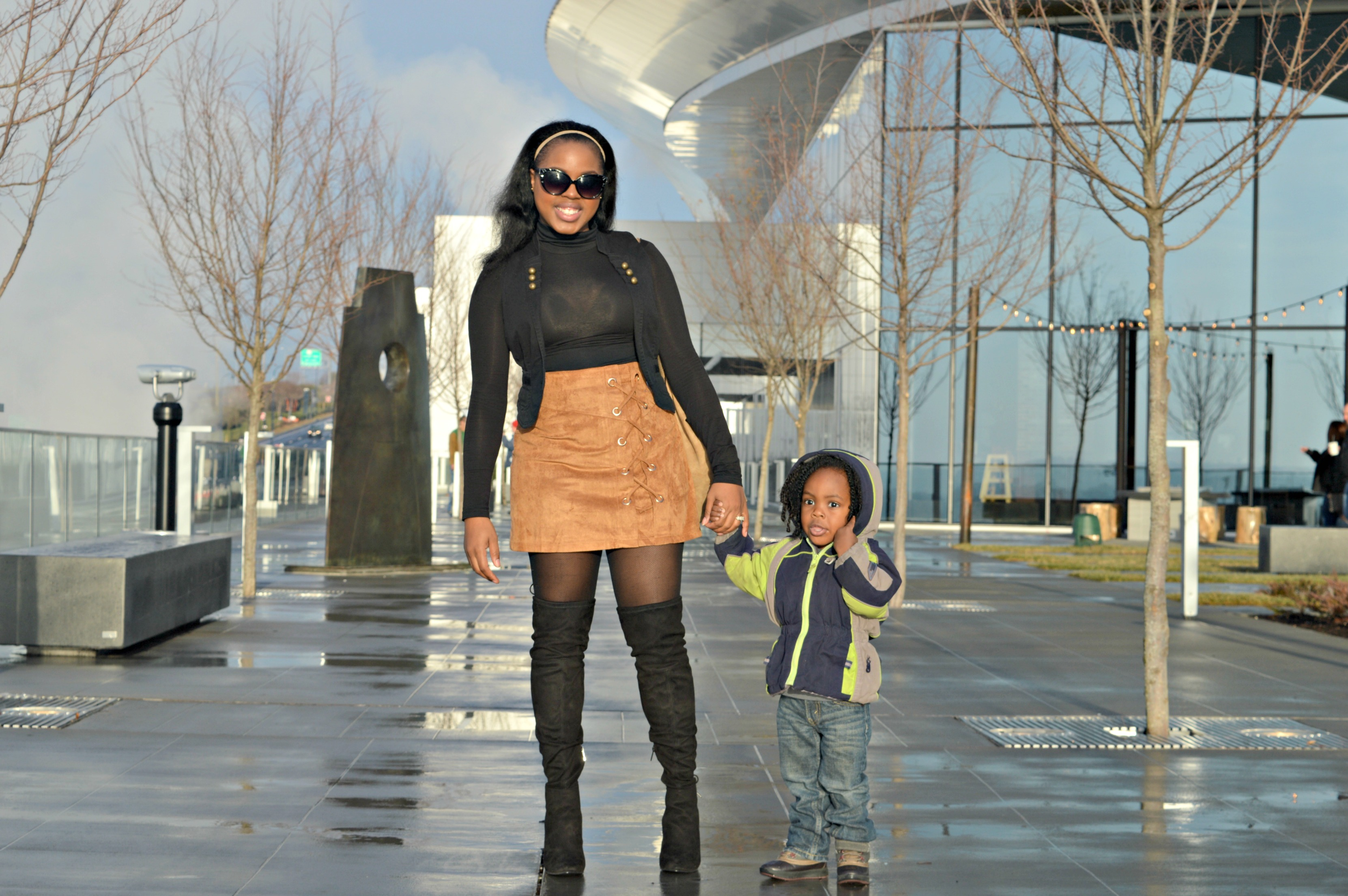 black mom- black mom and son- black mom with son- suede skirt- black over the knee boots- otk boots- black turtle neck-black vest